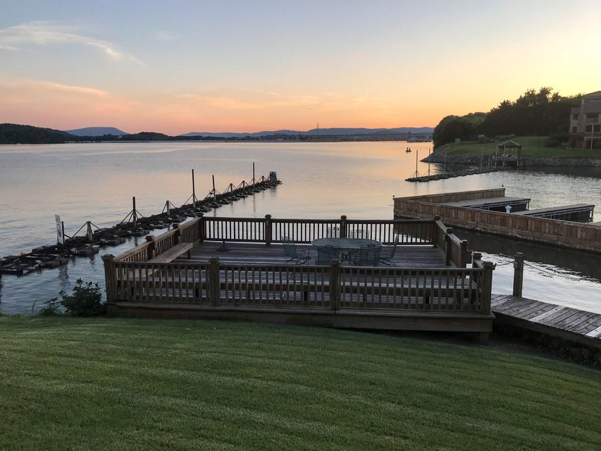 Breath taking view! Ground floor 2 bedroom unit that looks out towards the dam. Polished marble floors in all areas except the bedrooms. Large master with a sitting area. Stone fireplace in great room. Sunroom just off the great room. Covered boat slip #17 includes electricity and measures 32ft x 10.5 ft. included.