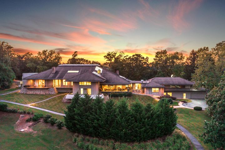 AS FEATURED ON HGTV'S ''POOL IN MY HOUSE'': Rare opportunity to own one of Chattanooga's most renowned estates.  This post mid-century modern home has been meticulously restored beyond its original beauty.  Located in the center of Chattanooga on Missionary Ridge with beautiful eastern views of the Blue Ridge Mountains and a western view of downtown Chattanooga.  Surrounded by 8.5 acres of lush landscape that includes tennis courts, putting green, walking paths and two iconic historical cannons. The home was designed by famous Los Angeles architect Harold W. Levitt who has created homes for the likes of film producer Steven Spielberg and actor Dean Martin. Levitt designed the perfect home for the family who appreciates luxury amenities, comfortable entertaining spaces and cozy intimate suites for privacy. The estate offers a private master wing with gorgeous views from it's private terraces.  His master bath has handsome walnut paneling with sauna, huge walk-in closet, and half-court hardwood gym complete with basketball goal and direct access to solarium. Her master bath includes dressing room with fireplace.  The bath is surrounded by opulent  calculatta gold marble walls and floors and features Jacuzzi tub, separate shower and the perfect walk-in closet with built-in shoe racks, glass front purse storage, and separate out of season cedar closet.  Four other bedrooms are located in the main living area.  All have large en suite baths featuring marble floors and counter tops, large walk in closets, build-in cabinetry and beautiful views. Two lower bedrooms have private terraces.    The study features luxurious walnut paneling, half bath and private terrace.   The heart of the home is the 88 x 53 Solarium which features a 30 foot high glass ceiling, heated indoor pool with diving board, reflecting pond, two changing rooms with showers, and newly renovated kitchen.  A sunken conversation area offers the perfect view of pool and surrounding landscape of live palm trees and foliage.    The music room is located off the solarium and features a wonderful entertaining bar complete with ice maker, sink and beverage refrigerator.  The formal living room features floor to ceiling windows and large stone fireplace.  A comfortable family room features a library with sliding ladder, stunning fireplace with artisan detail, screen terrace and large sliding walnut pocket door. The elegant dining room with marble floor seats 14 and it's own live garden. Large walnut bi-fold doors create an intimate space for dinner parties.  China and silver storage closet located just off dining room.  The gourmet kitchen is a chef's delight.  Stainless steel counter tops, large granite island, subzero refrigerator and freezer, three ovens, two dishwashers, trash compactor, gas range, gas grill, electric oven and large walk in pantry.  A separate butler's kitchen is loaded with storage, granite counter tops, sink, refrigerator and dishwasher.  The well appointed laundry has a private drying courtyard for air drying laundry, as well as dual stacked washer and dryers, folding station and drip dry rack with utility sink.  The apartment features two bedrooms with full baths, kitchen, den, private entrance, separate garage and patio space, allowing for long term guest stays or private in-law quarters.   Exquisite grounds have been meticulously maintained and feature several patios and terraces to enjoy the year round views of mountains including Blue Ridge, Signal and Lookout Mountains. Lighted tennis courts, putting green and a paved walking path are nestled among over 200 old growth trees, native plants and well tended lawns. This is a must see showcase home.  Buyer to verify square footage.