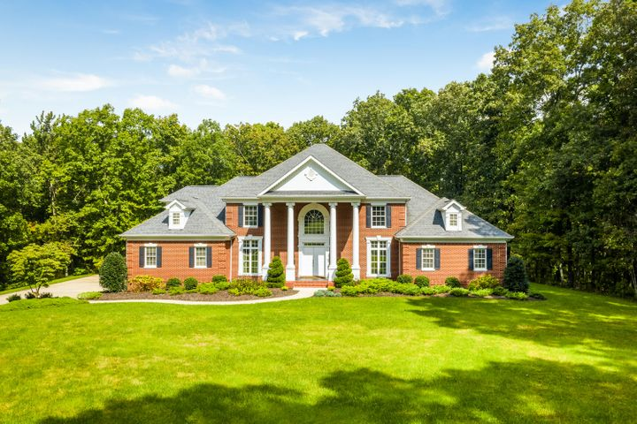 This gracious well built custom all brick home situated on 25+ acres offers all that a gentleman farmer could hope for. The two story entry welcomes you to hardwood throughout main floor, arched doorways & deep moldings. The enormous kitchen recently remodeled offers new cabinetry, gorgeous granite countertops, tile backsplash and new stainless appl.  The opulent master offers sitting area with gas fireplace and adjoining luxuriant bathroom with his and her vanities and walk in closets. The centerpiece of the den is the beautiful fireplace with custom mantle flanked by built in floor to ceiling bookshelves. French doors lead to stamped brick patio overlooking completely private yard and wooded property, great for entertaining family and friends. The second floor welcomes you to 4 spacious guest bedrooms, 3 adjoining full baths recently remodeled & bonus/exercise room. All freshly painted and carpeted. The horse enthusiast will enjoy the 3 stall barn, newly fenced pasture and pond. This home has been lovingly maintained inside and out.