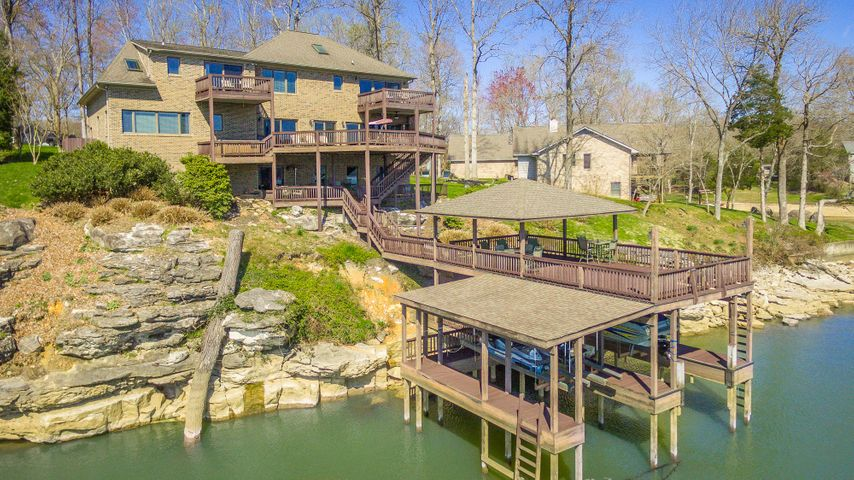 Invest in your lifestyle and live where you play. Life is better on the lake! This immaculate, all brick, custom, waterfront home has year around deep water, two-story boat dock, and one of Chattanooga's most spectacular views of the Tennessee River. There have been many updates throughout the home, including all Anderson windows and doors. As you enter the two-story foyer, you will notice the natural lighting from almost all of the rooms on the back of the home. The living room is open to the spacious den with wall to wall windows and glass sliding doors that opens to the covered deck and hot tub. The updated eat-in kitchen has granite countertops, tile backsplash, stainless appliances, and a pantry. The main-level also has a formal dining room and an office with a wall of windows to take in the water views. The upper level features two spacious master suites, each with their own private deck that captures the endless water views. There are also two additional bedrooms and full bath on the upper level. The third level offers a 23'6 X 14'11+/- bonus room. The lower level offers a rec room, exercise area, and a two-car utility garage. The main level has a two-car garage as well. There are multiple outdoor areas that are covered and uncovered that make this home ideal for entertaining. The oversized two-story boat dock has an upper level is partial covered and partially uncovered, boat lift, and two sea-doo lifts. There is also a rock seawall and located on a cul-de-sac street. Buyer is responsible to do their due diligence to verify that all information is correct, accurate and for obtaining any and all restrictions for the property. The number of bedrooms listed above complies with local appraisal standards only.