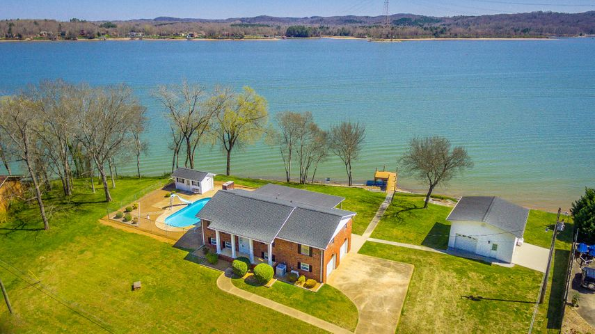 Own this prime piece of real estate with 265'+/- of water frontage on the MAIN CHANNEL with PANORAMIC VIEWS of the Chickamauga Lake and the Tennessee River. Ooh, living on the lake just became affordable in this immaculate all brick home that has been meticulously maintained inside and out. There is a stationary and floating dock, in-ground pool with slide and diving board, pool house with bathroom, and a detached outbuilding with garage and unfinished area (336+/- sq.ft) for storage, expansion area, or for a potential guest house. There is an additional 13 X 25'2+/- parking pad for boat/RV storage (if permit-able per restrictions). This low maintenance home offers 4 bedrooms, 3 full baths, formal dining room, den, eat-in kitchen, and a den/rec room with gas fireplace in the daylight basement. The garage is heated and air conditioned. You will LOVE the 37 X 12+/- upper covered deck and lower covered patio that extends the back of the home that captivates the deep water views. The number of bedrooms listed above complies with local appraisal standards only. Buyer is responsible to do their due diligence to verify that all information is correct, accurate and for obtaining any and all restrictions for the property.