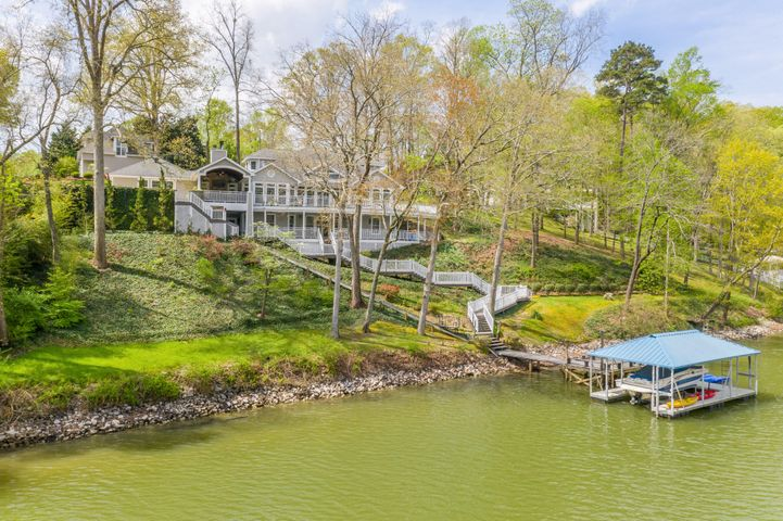 Surrounded by water and lush green space, you will find home as personal daily escape from the world while being convenient to everything Chattanooga.  This custom designed contemporary incorporates the best of urban, clean line architecture with open living spaces but a warmth desired in finding the perfect family home.  On approach, you almost miss it as this hidden jewel sits waterside with only its garage apartment hinting at its existence behind.The multiple outdoor areas, covered and uncovered capture its waterfront while expanding its living areas outdoors.  From the moment you enter, you are captivated by its views, its architecture and an abundance of natural light that fills every corner.  Two story family room with washed hardwoods overlooks water and opens to the completely up- dated kitchen professionally designed by Scarlett's that is not just gorgeous but incredibly functional for the family chef.  Comfortably flanked by the cozy keeping room with stone fireplace and eating area that extends outside to the covered porch for outdoor fireside dining or relaxing.  All overlooking the covered dock with accommodations for boat and jet skis with trolley from house to dock to easily load up for a day on the water.  With a total five garages, the detached garage offer's every man or woman's ideal cave with expansive storage for all the big toys. Garage apartment above the detached three garage is the perfect guest house which becomes essential when you home on the Chickamauga Lake.