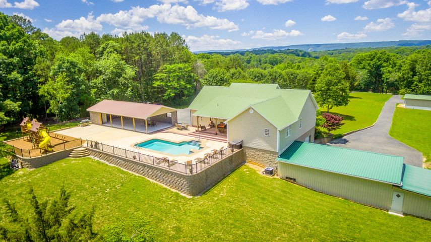 Just in time for summer fun! This home has all the potential possibly be the most fun house in Soddy Daisy! This amazing, custom built, one-level home is located on over 4+ acres and is being offered for the first time! When you drive up the private driveway, your oasis awaits but you will notice a very nice trailer home that was remodeled 6+/- years ago and makes for a perfect teen suite, in law living or even an income rental! The covered, rocking chair front porch is inviting and sets the tone for the cozy home. When you walk in the front door you are greeting with the vaulted ceiling living room with hardwood floors that opens up to the dining room and kitchen. The kitchen boasts a large island and even larger pantry! The large, main-level master bedroom has hardwood floors, en suite and TWO walk-in closets, one being the size of a bedroom! There are two additional bedrooms, one of which has its own private en suite. Off the kitchen is a bonus room that anyone can enjoy! The size can accommodate a crafter (built-in craft desks with storage will remain with the house), teens, or would make a perfect man cave and has a utility sink and it is plumbed for a washer and dryer! Upstairs has bamboo floors and even more space for whatever your need is...storage or an additional bonus room. Walk out the French doors in the dining room to a retreat in the backyard! You will feel like you're on vacation every day with the 12x28+/- inground pool with spa seats that is surround by stamped concert and aluminum fencing. Need a break from swimming, not a problem, because there is an incredible playground area that every kid will enjoy! After playing, and swimming, you can enjoy lunch or dinner under the covered pavilion with six ceiling fans! This pavilion has been the host for many weddings and parties and is rough plumbed for a half bath and an outdoor kitchen! When summer is over you can enjoy the fire pit area! When you're in the back yard, you have complete privacy with all