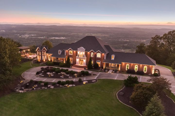 """This luxurious, professionally designed steel framed home is nestled in a gated community and offers stunning east/west views. The home is a masterpiece of design and craftsmanship featuring numerous regal appointments such as exotic flooring, exquisite Schonbek crystal chandeliers, elegant two-story foyer/family room with beautiful barrel vaulted ceiling, dual free-standing stairways, and custom, intricately handmade wood moldings. Updated gourmet kitchen has stainless Thermador high-end appliances, premium granite countertops, and large walk-in pantry. Choose either formal dining in the opulent dining room or entertain in grand style in the huge family room which opens up to the kitchen and large breakfast area and leads to an expansive wet-bar, a vast gathering room, and an octagonal room which is perfect for extra dining or playing a favorite card game. The sprawling entertaining areas continue outside to massive covered porches, a large covered pergola with outdoor kitchen, gas fire pit, sun deck, stone paved dance or partying area, and a heated """"endless"""" saltwater pool. Enjoy captivating sunsets from your downstairs master retreat which features a private portico, cathedral ceilings, electric fireplace, large plank maple flooring with walnut inlay, and circular stairs to a secluded loft. Romantic master bath includes dual vanities with gorgeous natural stone quartzite countertops, free-standing tub, and shower surround. The first-floor guest suite offers en suite bath, walk-in closet, and a private entrance from one of the porticos. Two full baths with double vanities serve four large bedrooms upstairs and bonus room. Call for an appointment today to discuss the incredible features this estate home has to offer!"""