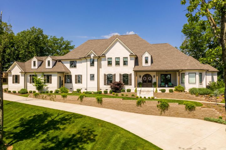 Don't let the opportunity of having two views, east and west, get away. This custom home built in 2017 is immaculate and high end throughout. This all brick estate was built on a double brow lot with every amenity in mind. As you enter the home you will notice the great care exercised to advantage of the sweeping views. A large open den with fireplace, tons of windows, coffered ceiling, hardwood floors through out the main level, open kitchen with large eating area all with panoramic views. There is also a relaxing sitting area off of the kitchen with gas log fireplace where you can relax and enjoy your morning coffee. The kitchen has two islands, two dishwashers, double ovens, large gas range, pantry, wash sink and kitchen sink, as well as tile backsplash and glass front cabinets. The master bedroom is located on the main level as well with coffered ceilings and hardwood floors and as a relaxing touch, there is a stone brook fountain running outside the master window so you can open it up and relax like you are in the wilderness. The master bathroom has an oversized soaking tub, double entry shower with multiple shower heads, and two walk in closets, one for her and one for him. The formal dining room, office, workout/flex room and huge laundry room with folding station are all on also on the main level. Upstairs you will find a guest bedroom with full bath, and 3 additional bedrooms, all with their own bathrooms. There is a media room, as well as a bonus room with bathroom. The exterior has a covered porch with gas log fireplace, outdoor kitchen, stone patio and is immaculately landscaped. This home has it all and more!!!