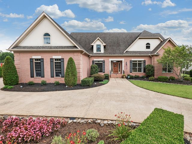 Brick home overlooking hole #10 fairway and view of green.  Impeccably maintained home with two story great room and grand two story entrance foyer.  The master on main features a fantastic walk in closet with adjacent laundry room.  The master has private entrance to covered porch and patio area overlooking golf course.  Upstairs is another home with 4 spacious bedrooms and a grand bonus room.  There are 2 full bathrooms upstairs as well as a stairwell to a large storage area that can be finished for additional living area if needed.  One of the upstairs bedrooms features a walk out patio with an elevated view of the golf course and manicured back yard and patio courtyard.  Spacious three car garage off the downstairs hall (hobby & storage area) and second half bath for the main level. Home also features the following:  - whole home water filtration and softener system  - trash compactor  - TVA Energy Evaluation System  - Anti-glare/fade protection film on southern facing windows  - Laundry chute from upstairs to downstairs   - Swing-out pantry shelves  - Motorized chandelier to lower for cleaning  - Built-in ironing board  - irrigation system  - Butler's pantry with sink and console/party ice-maker