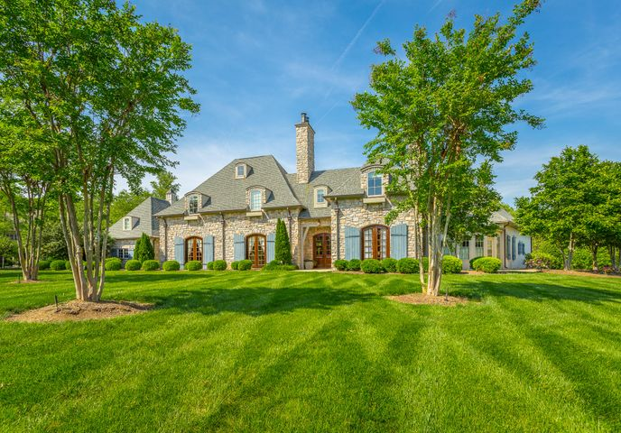 Showings will begin with Realtor Tour on Thursday, 6/20 from 11:30-1:30. Custom Built, Classic French Country home designed from Nationally Renowned Architect Jack Arnold's Le Jardin Plan featuring elements of Stone, Brick and Timber that highlight its Distinctive Curb Appeal. This home has so much to offer even for the most discerning Buyer. Entertain both inside and outside on the Veranda, Garden, and Pool Area. From the moment you enter thru the solid eight foot mahogany doors, the tone is set for exceptional living. Travertine tile, site finished hardwoods, generous baseboards and moldings reinforce the quality craftsmanship throughout.  The floor plan invites relaxation and an open flow with the grand living room leading to the separate dining room, spacious kitchen, eating area, and keeping room. The kitchen and keeping room exude the charm of French country design and are perfect for entertaining groups large or small. The kitchen is as functional as it is gorgeous and features a huge island for casual dining or extra room for entertaining.  It also provides space for all the cooks to be in the kitchen along with commercial grade appliances.  The keeping room features vaulted ceilings highlighted by timber beams and a stone clad fireplace flanked by built-ins.  Maximize your storage with the huge walk-in pantry just off the kitchen along with a spacious laundry room adjacent to the 4 car garage and one of the two staircases.  The main level library, study or music room with gorgeous wainscoting and its own private fireplace offers a cozy space to work or relax. Privately tucked away you will find the master suite that is truly a retreat on the main level. As you enter you will find a sitting area featuring curved wall and beamed ceilings separate from the bedroom that could function as a private den, nursery or just a get away to sit and enjoy a good book. The master bedroom is spacious and looks out over the garden. The master bath is spa quality with his an