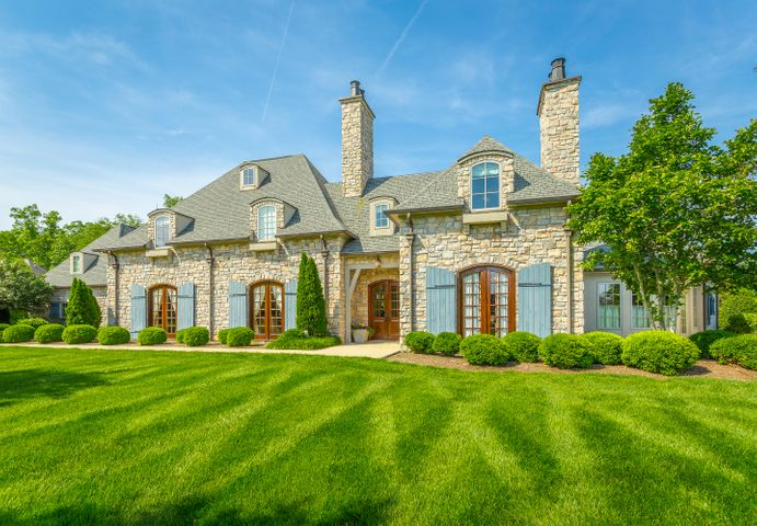 Showings will begin with Realtor Tour on Thursday, 6/20 from 11:30-1:30. Custom Built, Classic French Country home designed from Nationally Renowned Architect Jack Arnold's Le Jardin Plan featuring elements of Stone, Brick and Timber that highlight its Distinctive Curb Appeal. This home has so much to offer even for the most discerning Buyer. Entertain both inside and outside on the Veranda, Garden, and Pool Area. From the moment you enter thru the solid eight foot mahogany doors, the tone is set for exceptional living. Travertine tile, site finished hardwoods, generous baseboards and moldings reinforce the quality craftsmanship throughout. The floor plan invites relaxation and an open flow with the grand living room leading to the separate dining room, spacious kitchen, eating area, and keeping room. The kitchen and keeping room exude the charm of French country design and are perfect for entertaining groups large or small. The kitchen is as functional as it is gorgeous and features a huge island for casual dining or extra room for entertaining. It also provides space for all the cooks to be in the kitchen along with commercial grade appliances. The keeping room features vaulted ceilings highlighted by timber beams and a stone clad fireplace flanked by built-ins. Maximize your storage with the huge walk-in pantry just off the kitchen along with a spacious laundry room adjacent to the 4 car garage and one of the two staircases. The main level library, study or music room with gorgeous wainscoting and its own private fireplace offers a cozy space to work or relax. Privately tucked away you will find the master suite that is truly a retreat on the main level. As you enter you will find a sitting area featuring curved wall and beamed ceilings separate from the bedroom that could function as a private den, nursery or just a get away to sit and enjoy a good book. The master bedroom is spacious and looks out over the garden. The master bath is spa quality with his and her