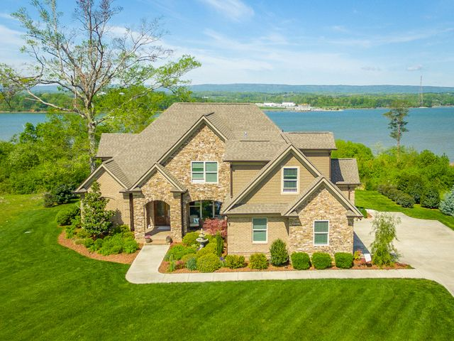 As you approach this spectacular custom home you will be greeted by the beautiful landscape, which includes an irrigation system and lighting all around. Upon entering, the beautiful soaring ceilings and crown molding will take your breath away as well as the astonishing views of the Tennessee River that can be seen immediately and from every room on the main level. This custom eat in kitchen boasts extremely high end appliances, granite counter tops, 4 burner gas stove, double oven and a huge pantry. The extra large island with hand picked granite is a cooks dream. The living room offers plenty of room for entertaining as well as a gas fireplace. The master on main has views to die for along with a large tiled shower, garden tub, double vanity, water closet and a large walk-in closet. The main floor is completed by the laundry room, half bath, office, dining room and the over sized 3 car garage which includes a gardeners dream space including a utility sink. Upstairs you will find 2 oversized bedrooms, one of which has an amazing river view, and a full bath complete with granite counter tops. There are 2 huge bonus spaces, which could easily be used as bedrooms, office, playroom , man cave or anything you desire, plus tons of storage. Enjoy outdoor living at its best on the custom concrete patio and did I mention the VIEW? The sunsets are absolutely unbelievable! Let's make this YOUR dream home...copy and paste this link to take our virtual tour https://my.matterport.com/show/?m=E2wL277adLM&brand=0  or call to schedule your private tour today. **agent has a personal interest, please see disclosure**