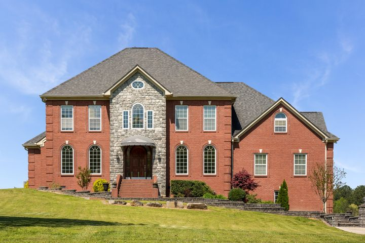 VIRTUAL TOUR AVAILABLE - RARE OPPORTUNITY to own a home with your own airplane hangar! Situated on a total of 2.4 acres (this includes the lot next door) backing up to Collegedale Municipal Airport runway. The home welcomes you with custom upgrades, tasteful design, and plenty of space. Step inside and immediately notice the stunning Brazilian Cherry hardwood floors and gorgeous staircase! The main level offers a spacious living room with gas fireplace, family room with gas fireplace, open kitchen with granite counter tops, breakfast bar and nook and stainless steel appliances, laundry/craft room, and a HUGE den with full bath that would make a perfect 2nd Master suite! The main master has its own study, walk-in closets, tiled double shower with 5 jets, and jetted tub. Also on the main level is a bright sunroom with its own gas fireplace, open kitchen with granite counter tops, breakfast bar and nook and stainless steel appliances, laundry/craft room, and a HUGE den with full bath that would make a perfect 2nd Master suite! The main master has its own study, walk-in closets, tiled double shower with 5 jets, and jetted tub. Also on the main level is a bright sunroom with its own gas fireplace, the perfect place to relax, entertain or watch the sunset! As you head upstairs notice the details on the custom staircase. Upstairs you will find 4 more bedrooms, one which offers its own deck, 2 full bathrooms, and a HUGE rec room. The basement has a great use of space as well, offering a workout/rec room which is also a storm shelter, workshop, 3 car garage, and a mother-in-law apartment fully equipped with living room, kitchen, bedroom, and full bath. If the inside wasn't enough than don't miss the 42x46 airplane hangar. If you don't have a plane, no problem, it would make the perfect storage for collecting cars, motor cycles, atvs, or whatever you desire. Some other details not to miss include RV parking spot. Septic is in front of home (so backyard is perfect for a future