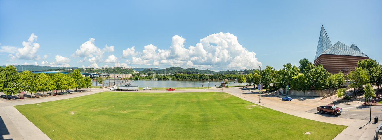 Investing in a lifestyle was never more true than when you call home River Pier in downtown Chattanooga overlooking the the gorgeous recreational Tennessee River. Featuring the most expansive covered balcony overlooking green space below and big water views. Get ''up front and personal views'' of the Coca Cola stage performances during Riverbend week without leaving home and protected from sun or rain is just one of the thousands of perks of conveniences offered. Located above such local favorites as Hennen's Restaurant, The Blue Pate and Cold Stone Creamery while flanked by the Chattanooga Aquarium and the Lookouts AT&T Field and only seconds & minutes of multiple other top tier local restaurants, shops and recreation. Walking and biking to work and play becomes a realistic option. With open flow from entry to end, this 2 bedroom, 2 bath one story condo offers a big urban lifestyle with the most well designed use of space. Living area, with sleek built-ins providing essential storage to include a convenient beverage center with two SubZero refrigerator drawers and wine cooler opening to the private balcony. Professionally designed  kitchen with furniture Viking six burner gas cooktop, SubZero refrigerator and quality cabinetry, expansive work and serve island, gas cooking and more cabinet storage than most 5000 SF homes. Luxurious master suite and sitting area offer commanding views of the water from their wall of windows and private porch. Master bathroom includes an oversized shower, separate vanities and customized closet.  All the  conveniences of a suburban home to include a separate laundry room and drop zone for all life's essentials. Enjoy all of the quality, amenities and views offered in multi-million dollar properties. Scale down the size of your home maintenance and step up quality and time to a richer lifestyle. *Optional basement storage unit available for $225 quarterly, in addition to quarterly HOA dues.