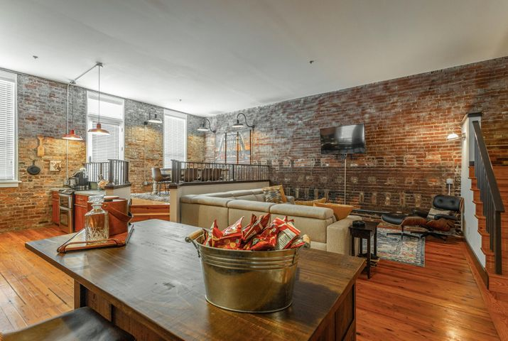 When is a condo not just a condo? When it is an experience!! You HAVE to experience this home! From the moment you step inside, you will know your home is someplace special! Time honored hardwood flooring, exposed beam ceilings, original brick walls - and that's just the master bedroom! Open concept floor plan plays hardwoods and brick walls against elevated and multi level living areas to make a feast for the eyes and relaxation for the rest of you! Cook's kitchen boasts stainless appliances, double oven (you know you will have guests when you live here and that extra oven space will be needed!), custom tile backsplash and solid surface counters. Elevated dining space is positioned for easy entertaining. Thoughtful storage space is plentiful throughout this home