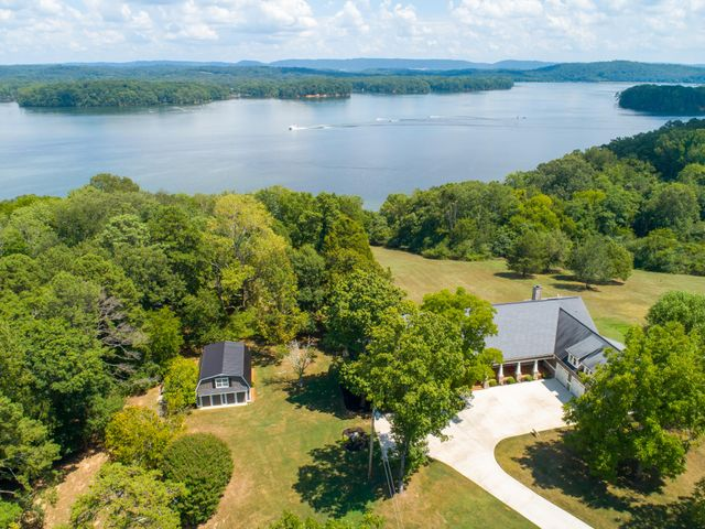 Let home take you away on two plus acres overlooking the very calm, soothing recreationally friendly big water of Chickamauga Lake on the majestic Tennessee River in the Greater Chattanooga area. Less than a mile to beautiful Chester Frost Park and a quick drive to downtown Chattanooga, this home and its grounds offer lower taxes just outside the city limits while surrounded in the lush green, pristine privacy of Big Ridge and beyond. Flawlessly renovated, updated and completely revitalized, this country estate offers expansive main level living with spectacular views from almost every room with multiple opportunities for covered outdoor living and breathtaking views from every direction. Spacious master suite is privately tucked away on the opposite wing from the guest bedrooms - two on the main level with one bedroom and oversized bonus room on the second level. Your escape will begin the moment you enter the driveway continuing until you retreat for the evening to the master suite with bedside fireplace to warm those crisp fall nights. Thoughtfully planned and designed to maximize open space from room to room, capturing every breathtaking water view with seamless results from covered front porch to the covered back. Daylight, walk-out lower level provides the perfect built-in cabana with sealed concrete floors, linear fireplace and full bath.  Two of the HVAC systems of three in the main house are dual fuel systems. Six garages, three on main level, one on lower level and two in detached garage with garage apartment above (square footage not included in total) - perfect guest house, nanny house or home office - work from home next door on your own property! Invest in your personal recreation, daily escape and live your BEST life, at home.