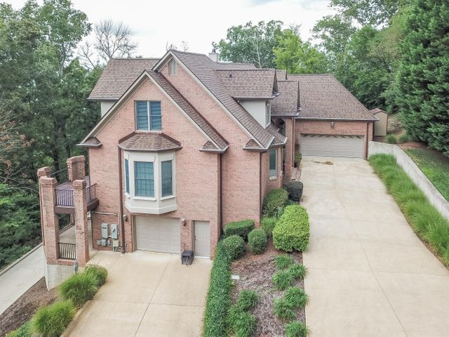 This well-designed and expertly-constructed custom home on over five secluded acres in the Frost Creek Farms neighborhood is loaded with upgrades, features and great space.  Past a private gate and up a long driveway is where you will find this all brick secluded mountainside retreat with a beautiful winter view surrounded by nature and privacy.  This four bedroom home, with a master on the main level, is updated with new decks, porches & patios, a swim spa, a fire pit, new Viking appliances, counters and a backsplash in the kitchen, a new roof, new generator, and more.  The full unfinished basement is climate controlled, includes an extra garage, has two covered decks, plumbing stubbed for a bath, and is ready to be finished.  Don't miss seeing this home; make an appointment today! Walk inside the artistic glass front door and stop to appreciate the two-story foyer, a grand staircase and a great room with floor to ceiling windows, a wood burning fireplace with a black granite surround and wood mantle, beautiful hardwood floors, a mount for a big television, surround sound, access to the back deck, sun room and built-in cabinets.  The beautiful hardwood floors continue into the formal dining room with chair rail molding, wainscot, deep dental crown molding and sound speakers in the ceiling that run off a master system.  Beyond the dining room the hardwood floors continue into the kitchen, keeping room, and breakfast room.  The kitchen is huge and completely chef-ready with an island, generous cabinets, drawers and counter space with an eat-up bar and beautiful granite counters.  You will also find a drop-in gas range on the counter as well as two convection ovens on the wall, microwave, dishwasher plus a dish sink and vegetable sink.  The kitchen is open to the breakfast room, with a dramatic, octagonal domed ceiling, as well as to the keeping room.  From the kitchen you can easily reach the enclosed, climate-controlled Sun Room with lots of windows, a ceramic tile 