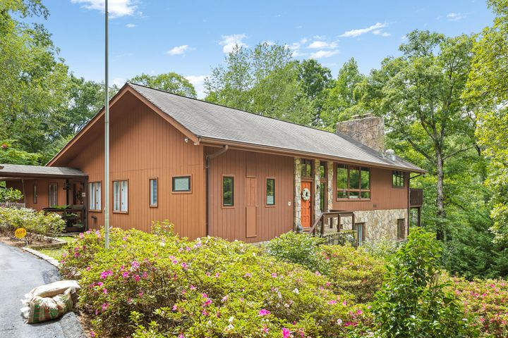 This gorgeous mountain chalet style home is sitting on 2.3 acres in the heart of the city, yet in a lake front subdivision.   A MUST SEE for your Lake Chickamauga enthusiasts! An abundance of windows and wooded privacy contribute to the tree house feel.  With 2 mountain stone wood burning fireplaces in the great room and basement family room, you can have your choice of where to curl up on those chilly winter nights. There is nothing cookie cutter about this unique and eclectic home, from the wood ceilings, modern kitchen, multiple level living spaces and real hardwood floors. Countless updates have been made within the last 3 years, from lighting to appliances to cabinets and counters, the list is too extensive to detail here.  For those with toys and outdoor hobbies, this home will not disappoint...For you there is a huge detached garage with a workshop and large 2 car carport that could easily store your boat or RV.  The detached garage is deep enough to accommodate 4 cars placed tandem with an additional workshop beyond the garage space.  There's also a year round scenic view of Lake Chickamauga from the house and access to main channel 3 acre community property for all the fun family activities on the water.   A list of all recent  improvements provided by the seller is available. If you are searching for the home that has it all, look no further!  Privacy, charm, waterfront community and close to downtown...this is the one you've been waiting for!