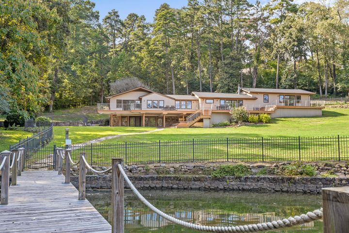 This private contemporary lake home evokes many of the modern mid-century design elements that blend perfectly with its natural surroundings. Banks of wooden casement windows and 2100 square feet of outdoor decking complete with stainless steel cable railings accentuate the view of the lake and surrounding grounds. A house for entertaining, both in design and function, it retains much of its original character with a custom knotty pine floor-to-ceiling wall with built-ins surrounding one of four gas fireplaces in the home.The centrally located kitchen, designed by Scarlett's Kitchens, features a custom granite island created from one enormous granite slab. Brazilian cherry cabinets with stainless steel pulls, pull out shelving, and an Italian porcelain floor complete the gourmet kitchen. Four bedrooms including the large Master Suite and Updated Master Bath with Brazilian Koa wood floors are found on the main level. The lower level has a large open room, mountain stone gas fireplace, a second kitchen and bedroom suite. This perfect in-law or teen suite has a separate private entrance, spectacular lake views and looks out on 1.8 acres and a large flagstone patio with a hot tub. With an irrigation system sourced by lake water, it is easy and cost effective to maintain the expansive grounds, mature trees and landscaping. The gently sloping manicured lawn rolls out to greet the lake and private dock. Additionally this home also has all new electrical, a recirculating tankless water heater and all new PEX Plumbing with hot water circulation system. A custom decorative aluminum fence surrounds the property and a separate two story guest house provides a lower level 4 car garage with a guest 1 BR/1 BA apartment on the upper level. Located in Hixson on prestigious Clematis Drive, this quiet tree lined drive is home to some of the most beautiful lakefront luxury properties in the area.