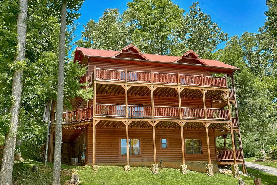 **Guaranteed over $80k Rental** Immaculate Cabin with everything you need for a getaway! This 3 story, 5 bedroom, 4 bath Log Cabin is a must see with Specatular views! It features a Theater room with statium seating and projection screen, game area with a pool table and air hockey table! Large kitchen with stainless steal appliances, kitchen island and breakfast bar, dinning area next to the kitchen. Large family area with stone fireplace and lots of windows! The large master features a seperate fireplace with 2 french doors leading to the wrap around deck! Ceiling fans throughout with cedar on the ceilings and walls!! The tri-level decks are a must see wether you want relax in the hot tub or entertain your guests!!