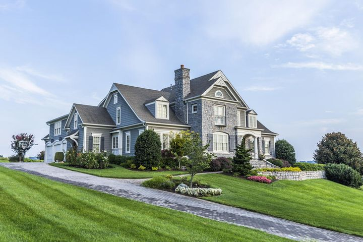 This classic New England style home combines the natural beauty of a boulevard building site with the exciting Southern Living plan, The Somerset, designed by Spitzmiller & Norris and built by Michael Bates Homes. Crafted of native quarried granite stone and James Hardie Fiber Cement Shake, the home was built to endure with low maintenance.