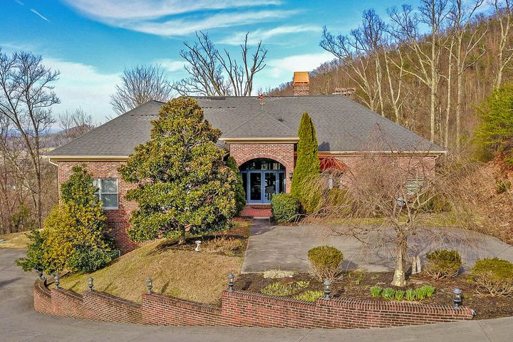 Outstanding views! Outstanding house! Overlooking Wears Valley, all brick home w/ copper accents provides plenty of space for entertaining & for expansion. Walk into the open  elegant foyer w/ trey ceiling. Continue into the formal living area(possible reading/game area), & enjoy the gas fireplace. Step onto the oversized screened porch from here or the kitchen &  listen to the peaceful sounds of nature while enjoying morning coffee or an evening meal. Enter the formal dining room(flexible space for living/game/pool room) & enjoy looking over the beautiful view. Continuing into the open kitchen & den, more stunning views to enjoy while prepping on the solid surface countertops & having ample storage for all kitchen needs. This end of the home is rounded out with a hall bath, 2 bedrooms,