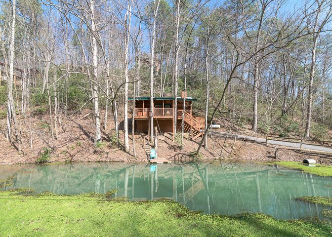 Adorable studio cabin overlooking it's own fishing pond! Located on a private lot. The cabin is on a .45 acre lot, and the adjoining .85 acre lotcomes with the property too (which has a fire pit and horse shoes set up on it)! Excellent location. Convenient to the Arts & Crafts Communityand only about 10 minutes to Downtown Gatlinburg. Features include an all wood interior, cathedral ceiling, fireplace, whirlpool tub, hot tub, covered deck, and a small fishing dock at the pond. Comes fully furnished and decorated. Owners rent this cabin on overnight rental and do excellent with it! In the 1st 365 days that the owners rented this cabin, gross income is $45,009.11.
