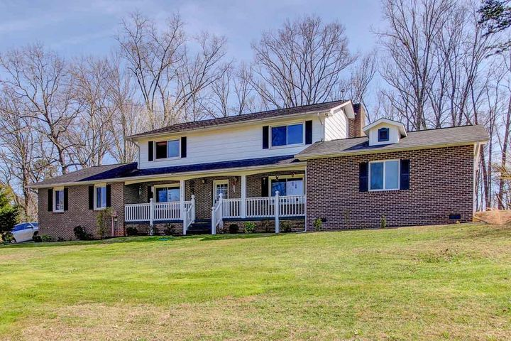 Quiet country living awaits you in this exceptionally spacious home on over an acre less than 15 minutes from downtown Sevierville. The main level of the home centers around a living/family room combo with custom wood trim and a brick fireplace with gas logs. The kitchen features a gas cooktop and built-in oven, island, and plentiful cabinet & counter space. It opens to the dining room with lots of natural light. The roomy main-level master offers a walk-in closet and ensuite with custom tile shower. A powder room, laundry room, entry/mud room, and attached garage round out the main level. Upstairs is a second master with private bath, two bedrooms sharing another full bath, plus a bonus room with closet. Outdoors there is a covered rocking chair porch in front, plus a covered deck/patio