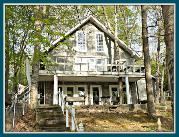 Douglas Lake Front chalet! Home is nestled in a wooded setting with easy access down to the dock area. Fenced back yard. Granite counter tops in the kitchen. New roof in 2012. New HVAC in 2018. 2 Bedroom septic, but home can accomoodate additional guests. This is the perfect lake front get-away you've been looking for to create memories that will last a lifetime. Great for vacation or permanent home. Located at the end of a cul-de-sac. 220 wiring for a hot tub. Lower level wet bar. Boat dock is included. Home is selling completely furnished.