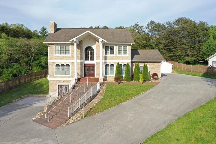 This exquisite brick and stucco home is situated in the heart of Pigeon Forge! This home has been updated top to bottom and is well suited for entertaining. Equipped with 2 main level kitchens, and a full kitchen downstairs - downstairs can be used as a complete separate living area - and a large 23X20 gazebo with full kitchen and half bath, all of your entertaining needs will be fulfilled. 5 Bedrooms and 5 baths - 2 of which are master ensuites - provides you plenty of room. Tigerwood and marble tile enhance the magnificence of this extraordinary property. The custom main kitchen is incredible. Complete with large island, marble tile, and quartz counters to accent the rustic custom cabinetry and stainless appliances. This home is a must see