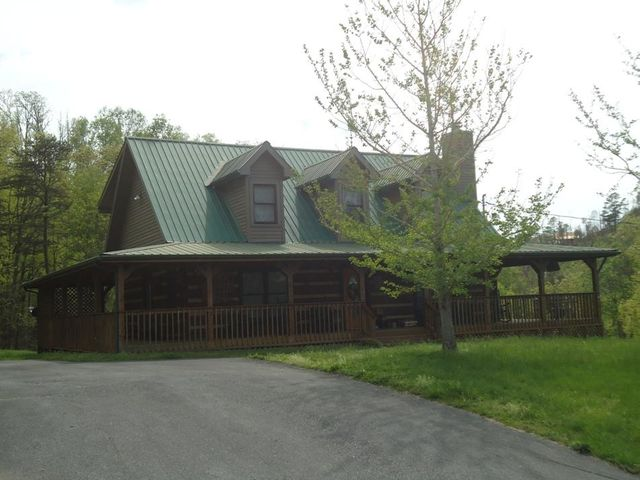 Fabulous True Log Cabin in beautiful Wears Valley. Perfect location for your Smoky Mountain residence, a special private get-away location or an income producing vacation rental. This cabin is perched on a slight rise on a .92 acre gently rolling lot with wooded and moderate mountain views. The wide covered wrap around porch goes completely around the cabin with a portion at the rear screened in to make a  wonderful spot for enjoying morning coffee or dining outside. On the main level of the cabin is a living, dining and kitchen in the great room style along with a large master suite, a guest half bath and a laundry room. The spacious living room has a stone gas log fireplace, decorative mantel and hardwood flooring.