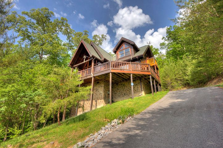 Smoky Mountain Dreams come true in this all wood three bedroom, two and a half bath home with vivid views of Mount LeConte and Cove Mountain. Nestled on almost three acres of private wooded lot this elegant cabin boasts of a master bedroom on main floor, gourmet's delight full kitchen, with updated appliances and a wall of windows to take in the views while you cook or relax in front of the mountain stone fireplace. Grab your coffee and step out on the partially covered, wraparound front deck to enjoy the mountain views or sit out and listen to the rain on your covered back deck. Upstairs you will find double the guest space with two more ample bedrooms and an open loft. There is even a private ''Romeo and Juliet'' 'Balcony off one bedroom. Plenty of closet and cabinet space make this cabi