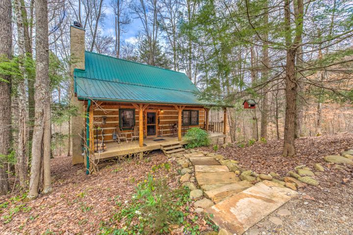Charming two bedroom, two bath log cabin in a serene wooded setting 15 minutes from the Pigeon Forge Parkway in the gated community of Walden Cove. This hand-hewn log cabin on 0.79 acre is the perfect private retreat with no rentals allowed. Gorgeous stone wood burning fireplace with blower, hardwood floors, loft with pool table and a screened porch. Walden Cove is a 162 acre community and wildlife sanctuary. Owners enjoy the use of these acres including a pavilion with stone fireplace, barn, fields, and Walden Creek. Underground utilities including cable and broadband internet. A must see! Home sold furnished with exceptions. 1 Year Home Warranty.