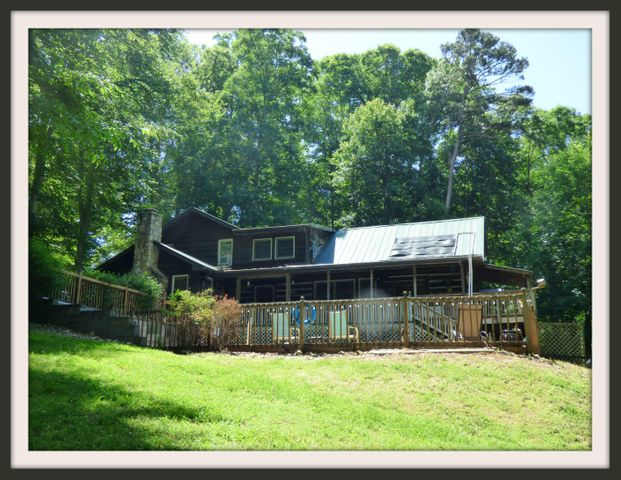 Douglas lake front home in a secluded wooded setting. Exposed beams in the family room overlooking the pool and lake, recreational area and gas log fireplace. Beautiful wood burning stone fireplace in the very spacious living room. Solar heated Gunite pool. Lot allows for a easy stroll down to the lake with permitted dock. Bedroom and bath main level and 3 bedrooms 2 baths upper level. Lower level partial basement with gas heat not included in the Total finished Sq Ft. Hot Tub. The yard is fenced for pets. Boat access road down to the lake. Split unit HVAC. Two additional sleeping quarters.