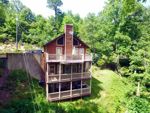 UNBELIEVABLE BUY ON THIS INCOME PRODUCING 1BR/2.5BA CABIN WITH BONUS ROOM! Take in the breathtaking mountain views from one of the three levels of decking, or soak in the hot tub while enjoying the peaceful and serene mountain setting. This cabin is top notch and is in pristine condition inside and out. Interior features include wood walls and vaulted ceilings on main level with a nice open living room with stone fireplace. Spacious fully equipped kitchen for dining. Arcade game table just added! Each of the lower levels feature King Master Suites with coffee bar and mini fridge for the enjoyment of the guests. This cabin is being sold fully furnished and turnkey ready to go. Recent upgrades include vinyl plank flooring on all levels, paint, bedroom furniture