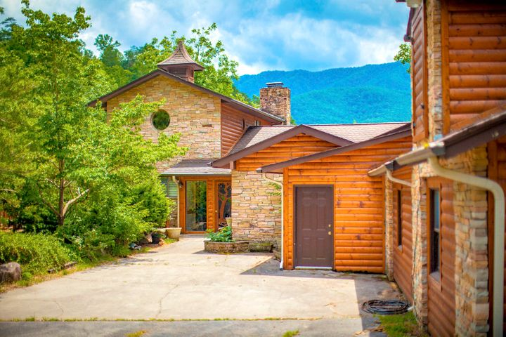 Nestled in the highly sought-after community of Cobbly Nob near Gatlinburg, and surrounded by majestic views of the Great Smoky Mountains, you will find this authentically constructed 8BR/7BA log & stone lodge.  Situated on over 5 private acres, the three levels of open living space with over 6,200 sq.ft under roof that offer exposed beams, tongue & groove ceilings & walls throughout the main living area, and a wall of windows for that enchanting mountain getaway experience! The fully equipped and spaciously designed kitchen is complimented with a professional grade Wolf Gas Range with a unique range oven hood, stainless steel appliances throughout, a kitchen island and bar, and an abundance of storage and cabinet space.  Enjoy the 3 private community pools and tennis by the main entrance!