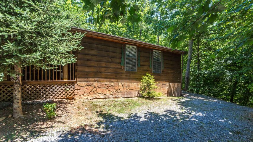 Great location between Gatlinburg and Pigeon Forge. This park model log cabin is a terrific investment opportunity. It sits perched on a wooded hill in Sky Harbor. It has tongue and groove wood walls, a cozy cabin atmosphere with log beds, a hot tub and a nice deck to enjoy your private wooded setting.  There is a 1 BR septic permit but the cabin has 2 private sleeping areas.  The shared driveway is steep but there is plenty of parking at the top.