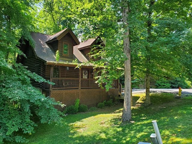A spaciously designed four bedroom cabin is nestled in a log cabin community with a natural wooded, mountain setting and a year round creek in the back. This cabin is easily accessible and just minutes away from restaurants and entertainment, with the benefit of no steep roads to get to the cabin. Upon entering, you will be welcomed by a very open floor plan of rustic charm with cathedral ceilings, stack stone fireplace & plenty of windows. Plenty of room for everyone to relax & enjoy! As you ascend upstairs you will enter the Master suite with large whirlpool tub & full bath w/shower. The upper level also has a loft bunkroom for the kids.There is one bedroom on the main level and 2 additional bedrooms located on the lower level with a TV room for the perfect movie night.