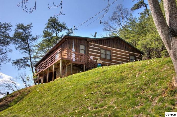 On over one acre this true log cabin has beautiful mountain views of Mt. Leconte and the National Park. Pristine farms stretch out below you...Easy drive from Pigeon Forge or Sevierville just minutes to all the attractions, dining and shopping but so private! Wrap around decks, hot tub,whirlpool tub, 2 full baths, log furniture stays and no HOA fee. So much to love! in this open floor plan with with vaulted ceiling. Wood burning fireplace can be converted to gas as line is present. Metal roof makes this cabin easy to maintain. It is doing very well on rental program making around $30,000 annually.