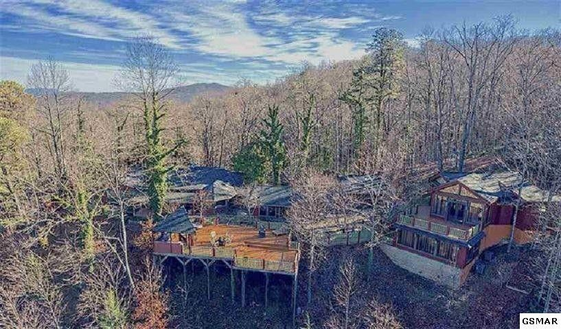 Seller open to a creative Lease or Lease Purchase to get you into this wonderful property! Call for possibilities! Located in one of the most prestigious and history rich communities of the Great Smoky Mountains ''Norton's Creek.'' Custom built grand estate right next to the national park with gorgeous views! No expenses were spared in creating this one of a kind log cabin with three car garage, guest house and tree house!The hand crafted features throughout this stunning property are endless from the moment you reach the gate. From the artisan birdcage lighting that line the driveway, custom laid brick courtyard, three car carriage garage with wood bark finish, Brazilian Mahogany hand carved front entryway, lighting and decor custom all the way from Turkey.