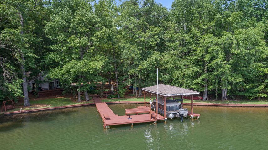 Home nested in trees on Large FLAT lot with seawall, pier and boatlift.