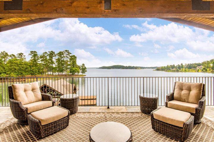 WHAT ELSE COULD YOU ASK FOR?VIEW, VIEW, VIEW! Dare to be impressed.Incredible lake home w/ luxurious finishes with a sophisticated rustic feel.It is like having 4 Master Suites. Large covered Porches w/ fantastic views. 208+- WFT. Over the top features with flagstone hardscapes on the lakeside in shapes of benches, tables and walls of lush ferns, stone water features, golf cart garage and water toy storage.Hot Tub, Covered Boat house with lifts, 2 outdoor kitchens,screened porch on main level, 5 bedrooms,7 baths, Iron Gated entry, dble. garage & guest house, upscale appliances, central vac, generator, wet bar, kitchen island,limestone mantel,2nd kitchen in lake level living area & exquisite lighting fixtures. Located on the East side of Lake Martin convenient from Bham, Atlanta and Auburn.