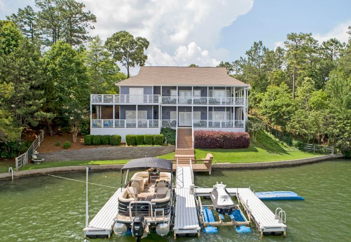 Location,Location, Location! View, Deep Water, Lakestyle home, Covered porches and boat storage in one of the most popular Eastside communities call Longleaf. This well maintained and cared for vacation home has 4 bedrooms,3.5 baths, 2 levels with living area on each, wood finishes throughout, easy access to the lake and floating boat dock with boat lifts. The multiple outdoor areas provide a private area for sunning or relaxing on the covered porch and enjoying the great view of the main part of the lake,but in a calm area great for swimming. Grilling out on the covered porch just off the large kitchen makes for great entertaining. The nice wood cathedral ceiling in the living area compliments the fireplace and hardwood flooring. The breakfast bar is great and the stainless appliances.