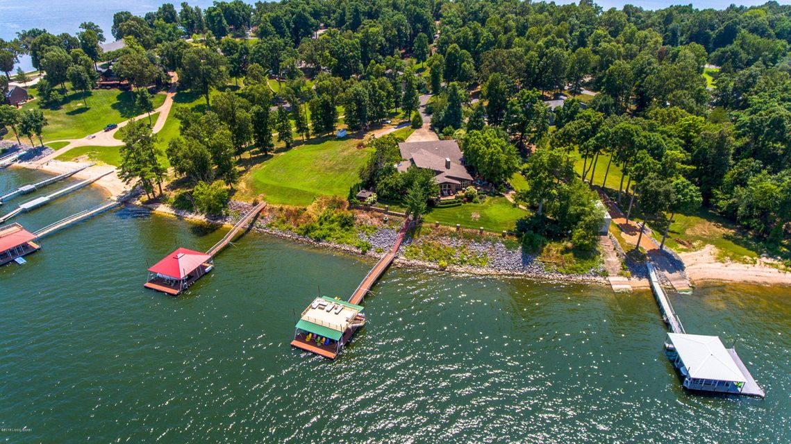 Paradise awaits you at this Kentucky Lake home. Home boast expansive views of Kentucky Lake and positioned just across from the Kentucky Dam. Originally constructed in 1940, this cedar and stone home has been professionally expanded and updated over the decades. Upon entering home you are greeted with vaulted ceilings, impressive exposed beams and a direct view of the water ahead. The open floor plan flows from foyer into kitchen and living room. With multiple doors leading to patio, this home is ideal for entertaining. Each bedroom offers private patio access. The master bedroom is truly a suite offering 25' of floor to ceiling windows with uninterrupted views of the lake, wood burning fireplace and master bath with large walk in shower and soaking tub. The outdoor living areas have