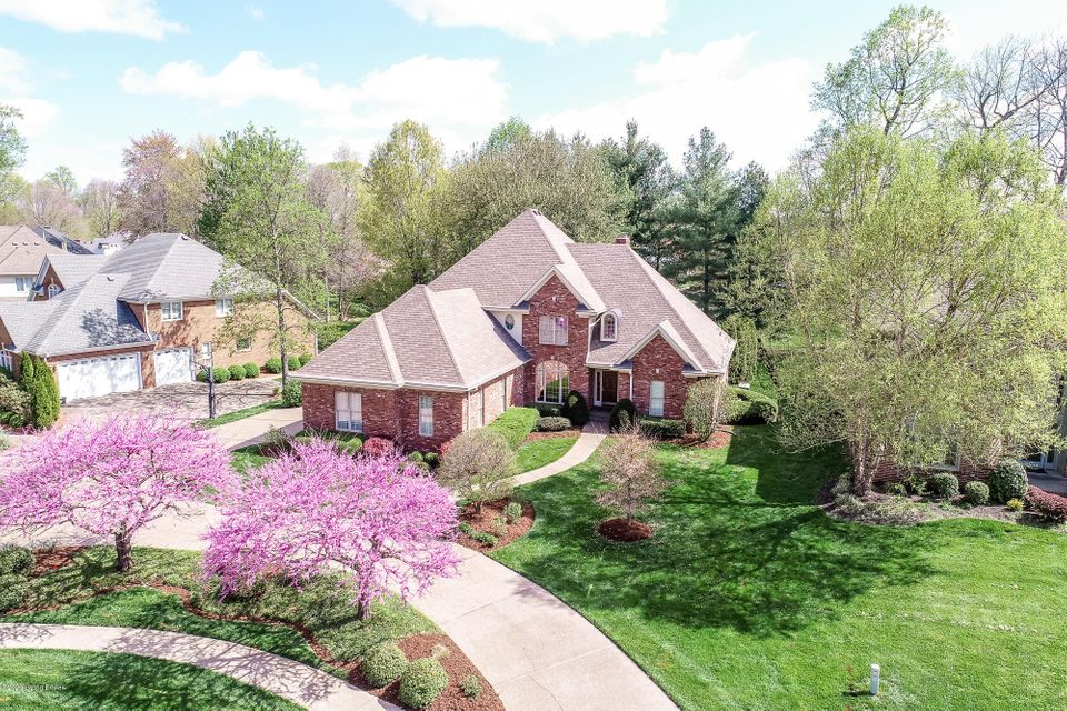 Spacious, 2 story home in the desirable Sutherland neighborhood of picturesque Prospect, KY! Situated just along River Rd & Hwy 42, you can enjoy the respite offered in this beautiful corner of Jefferson County while an easy & scenic commute takes you straight into downtown Louisville. A circular drive welcomes you onto the beautifully landscaped .46+ acre property. From the entry foyer you'll find the formal dining room & the 2 story great room with corner fireplace & floor to ceiling windows offering views of the beautiful pines lining the backyard. From there you'll find the spacious Eat-in Kitchen with center island, & beautiful granite countertops overlooking the breakfast area & sunroom, all with hardwood flooring. Just off the sunroom, enjoy the outdoors, regardless of the weather,