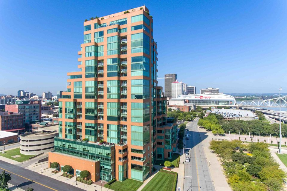 An exceptional unit of Louisville's most renowned luxury high-rise, this gorgeous condo offers buyers a rare opportunity for the building, built with the footprint of two spacious units combined, featuring double the views, living spaces and storage of a typical unit. Less than a decade old, this stunning condo blends the style of a contemporary city penthouse with the ambiance of a riverfront getaway, all while still conveniently tucked within the heart of Louisville. With sweeping panoramic views, hardwood floors and designer lighting, the main living space of the unit has been custom designed for enjoying time with family and friends, featuring an open floor concept with formal dining area, unique platformed sitting room overlooking the Ohio River, living room with elegant fireplace and