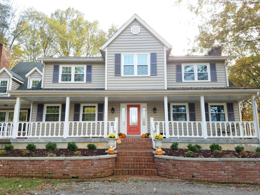 Rare find in much-desired location. Charming, updated home nestled in serene wooded setting offers country living just minutes from the freeway and city conveniences. Sit outside on the tranquil wrap-around porch overlooking the pond, or stay inside where this home's many windows bring the park-like setting indoors. The spacious kitchen is perfect for the home chef, with granite counter tops, new GE gas stove, oven, refrigerator and dishwasher. This is a perfect home for entertaining or family get togethers, with a separate bar area and new patio. Some of this home's finer touches include refinished hardwood floors, custom cabinetry, moldings and built-ins. Two fireplaces (one gas, one wood-burning) add to the inviting feel. The mud room leads to an oversized laundry room, with extra