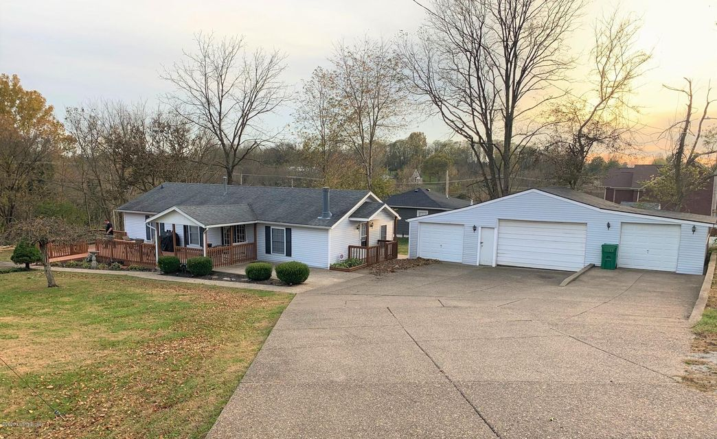 Welcome to this very cute and well maintained ranch home that sits on an almost 1/2 acre lot and has a 4 car detached (20x46) garage.  The garage has 3 separate bays, two 1 car and one 2 car bay and a huge driveway with lots of room for parking.  Walk up the sidewalk to the 11x12 covered front porch and an 11x35 connected deck. The great room has a beamed vaulted ceiling with ceiling fan and a corner creek rock wood burning fireplace.  The great room opens to the dining area.  The kitchen has lots of counter space and cabinets with wall pantry and built in trash can.  Nice size primary bedroom with walk-in closet and private bath. Small 2nd bedroom.  Separate laundry room.  There's a coat closet in the great room