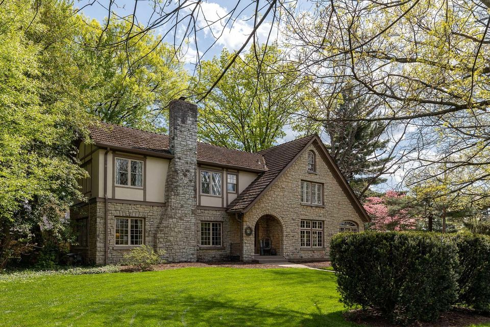 Quietly nestled among mature trees, manicured landscaping, and sprawling lawn, this timeless Tudor Revival home sits thoughtfully positioned at the rear of a Cherokee Gardens' corner lot. Featuring access by private side road, the incredible stone and stucco home offers a rare opportunity for the Lexington Road corridor. One of the original six homes built in Cherokee Gardens, this historic home has been exceptionally preserved yet carefully improved upon, offering an updated eat-in kitchen with open floor plan, stylish library addition, spacious primary suite, renovated bathrooms, and much more throughout the home's nearly 3,200 sq. ft of stunning living space. Past an arched stone entryway, guests first arrive into the spacious foyer of the home, featuring hardwood floors, tall ceilings,