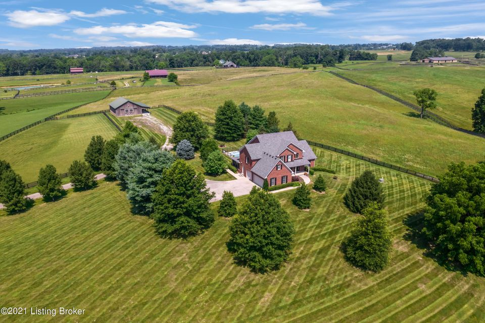 QUINTESSENTIAL KENTUCKY! Amidst rolling fields of grazing horses, this lovely home is perfectly situated in the prestigious equestrian community of L'Esprit. PEACE abounds on this gorgeous 13.33 acres, complete with an EXCEPTIONALLY MAINTAINED home, IN-GROUND POOL and 1700+ sf BARN. The ''wow'' strikes the moment one enters the foyer and sees the view out the back palladium window overlooking the pool. Enjoy EASY and ELEGANT living with a 1st-floor Primary Bedroom Suite, Laundry and garage access. The floor-plan is perfect for entertaining, too, with a circular flow, big and bright rooms, hardwood floors, built-ins, gourmet kitchen and more! The upstairs bedrooms are sizable, with a bonus room for play or work! The walkout lower level features a 2-sided fireplace, wet bar, office and bath.