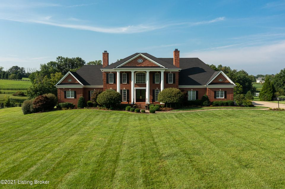 The exceptional location of this brick Georgian home set on 5 acres in gated Majestic Oaks in the heart of saddlebred horse country is second only to the fabulous interior of this Blacketer built home with open floor plan, top of the line finishes and woodwork and ideal for entertaining and luxury living. Double glass front doors and Greek columns welcome you as you enter the massive center hall with curved staircase, wainscoted walls and 20 feet ceilings. The wood paneled living room on the left features built in bookshelves and cabinetry and a gas fireplace with marble surround. The dining room also features wooden paneling throughout with wainscoting, gas fireplace with marble surround and built- in fluted shelving and cabinets.