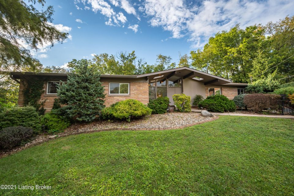 This stylish and sleek Mid Century Modern home has been thoughtfully updated honoring the original aesthetic and style. It is conveniently located on a secluded cul-de-sac in Rock Creek, overlooking the green of hole 16 at Seneca Park golf course. From the stone walkway, enter the home through beautiful double doors and you're greeted with striking vaulted ceilings, walls of expansive windows, modern hardwood floors, and a spacious, wide open floor plan that has been updated throughout and flows perfectly for entertaining family and friends. The kitchen has been completely updated with Kitchen Craft Soho modern tongue and groove, real wood, soft close drawers and cabinetry. Dimmable under mount LED task lighting sets the mood, and gleaming Caesarstone Quartz countertops accent a 12-foot
