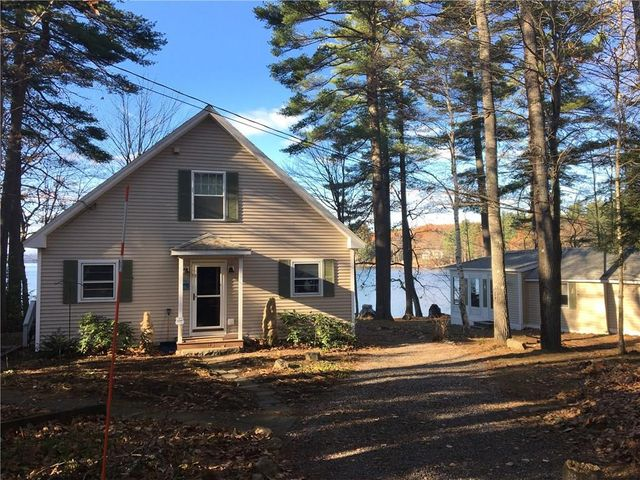 View from the driveway facing the front with the detached 1 Bed, I bath cottage on right. Long Lake can be seen in the rear